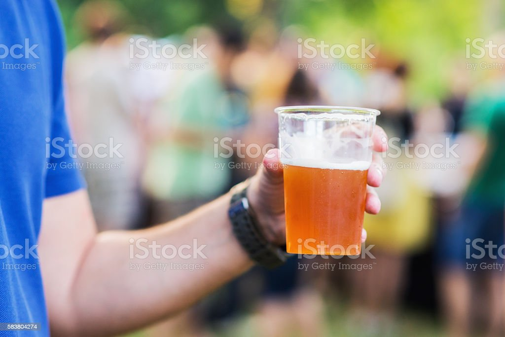 Man having fun while drinking beer shot at party concert stock photo