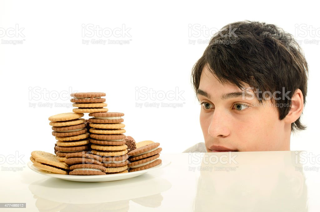 Man having in front a lot of sweet dessert. stock photo