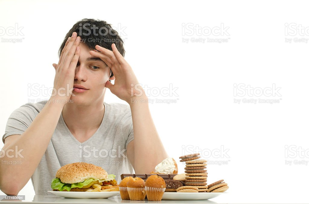 Man having in front sweet dessert and a big hamburger. stock photo