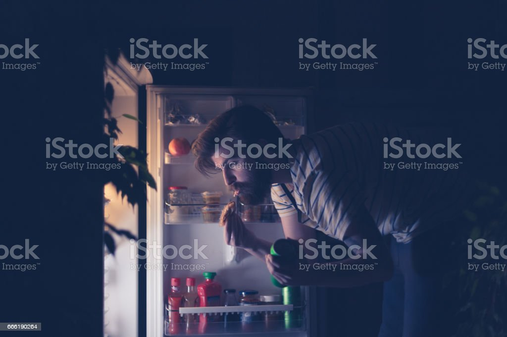 Man having snack and drinking beer late night in front of the refrigerator stock photo