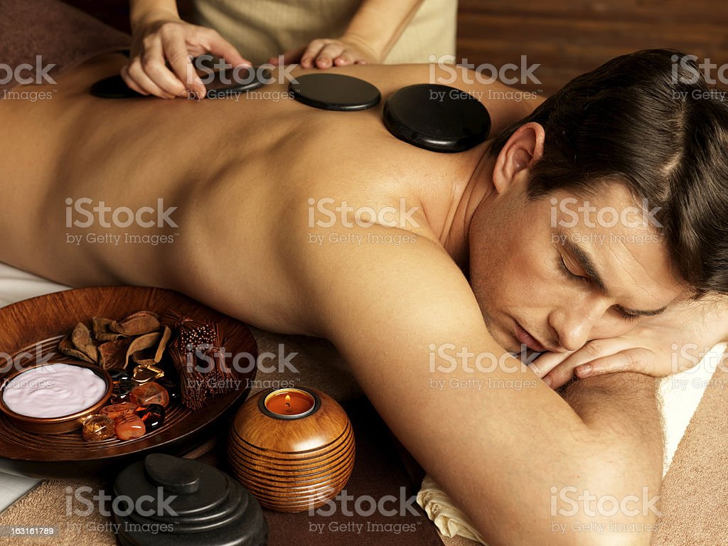 man having stone massage in spa salon stock photo
