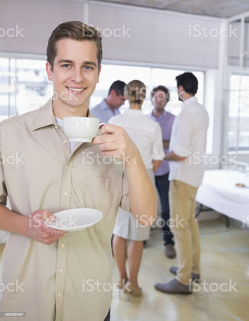 Man having tea with colleagues in discussion behind at office royalty-free stock photo