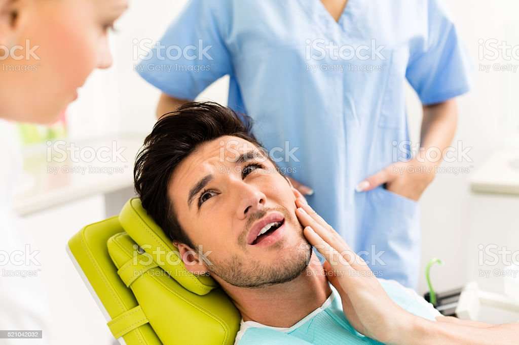 Man having toothache at dentist stock photo