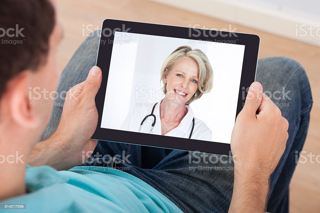 Man Having Video Chat With Female Doctor stock photo