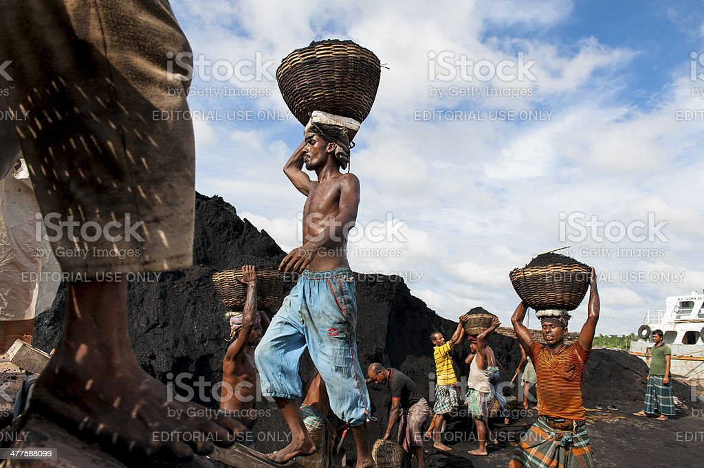 Man heading coal in barrel walking on single board royalty-free stock photo