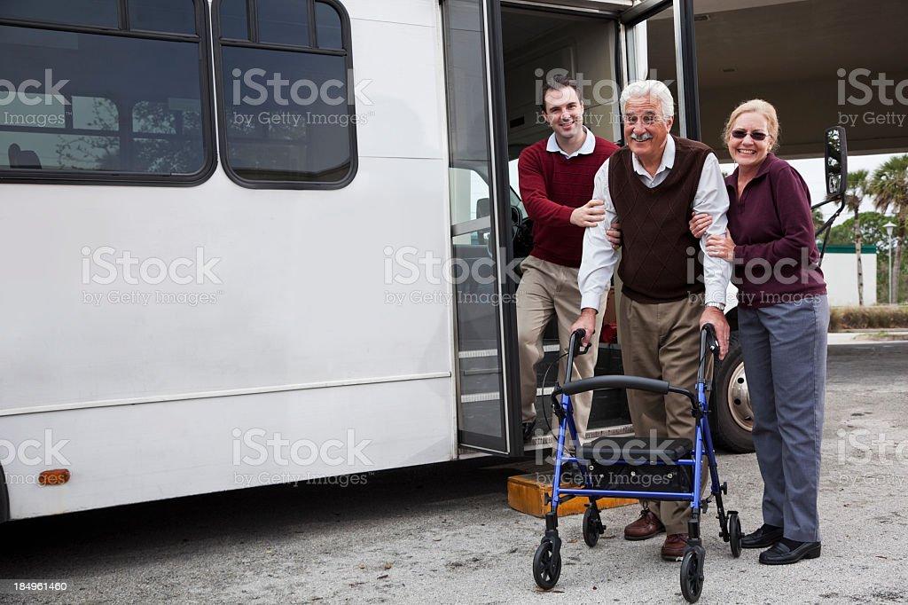 Man helping senior couple outside shuttle bus royalty-free stock photo