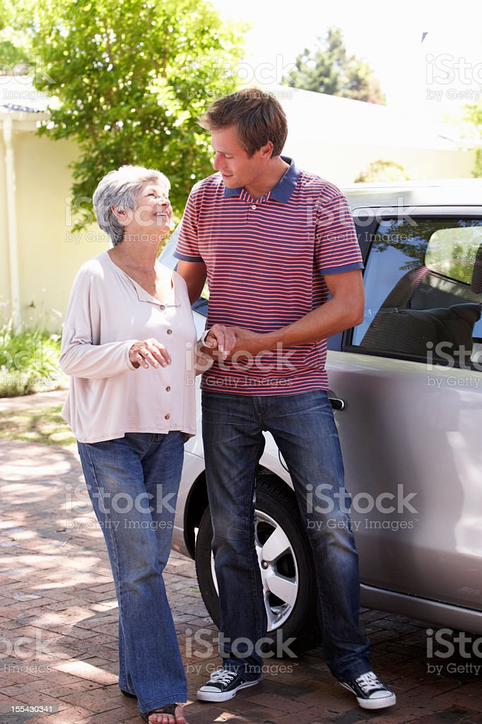 Man Helping Senior Woman Into Car stock photo