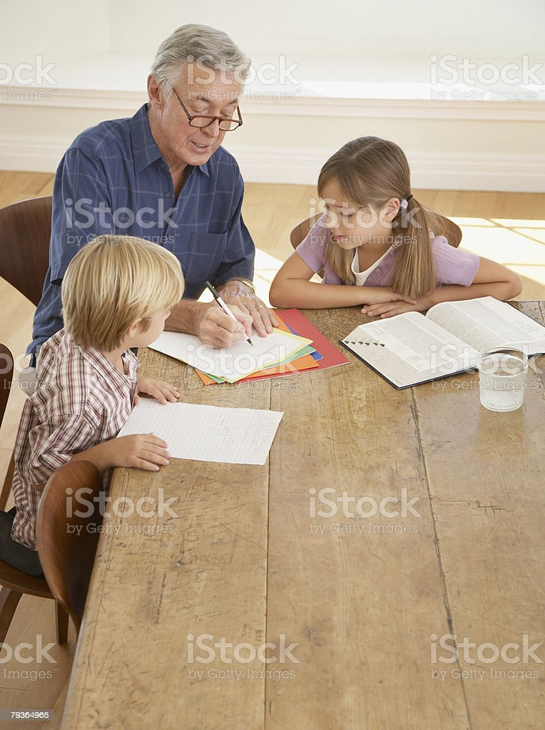 Man helping two kids with homework at kitchen table stock photo