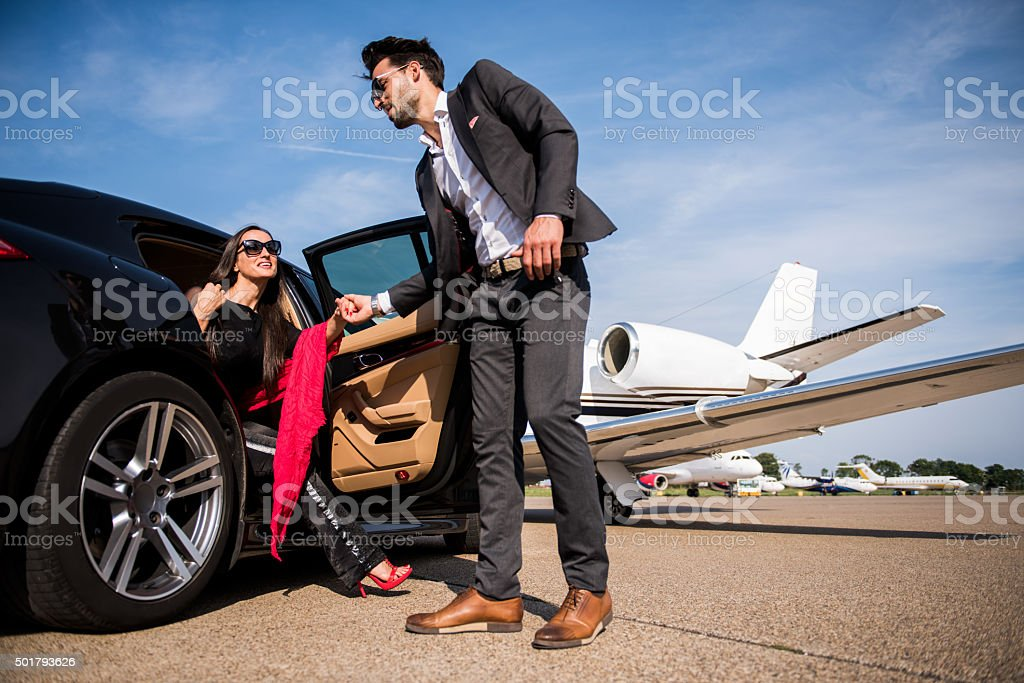 Man helping woman to exit the black vehicle stock photo