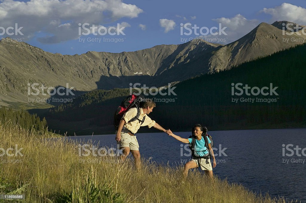 Man helping Woman up Hiking Trail royalty-free stock photo