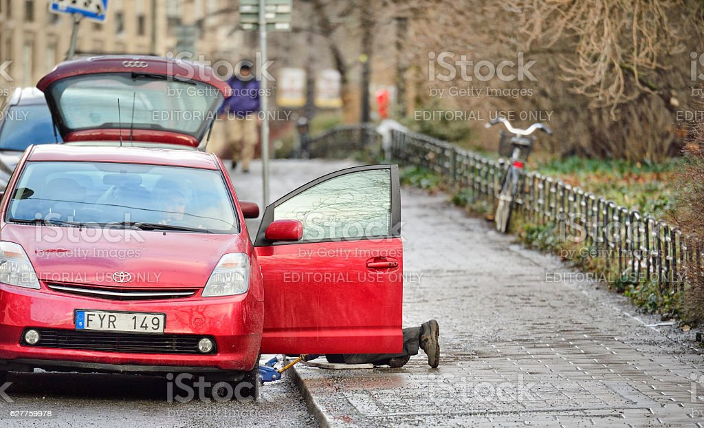 Man helping woman with car tire puncture stock photo