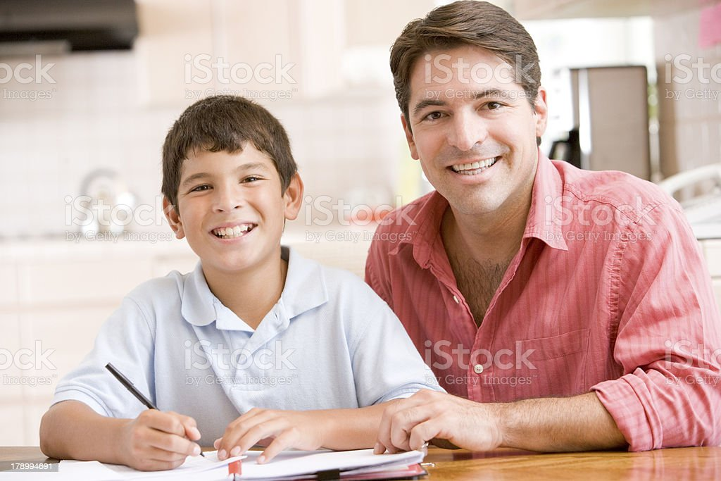 Man helping young boy in kitchen doing homework royalty-free stock photo