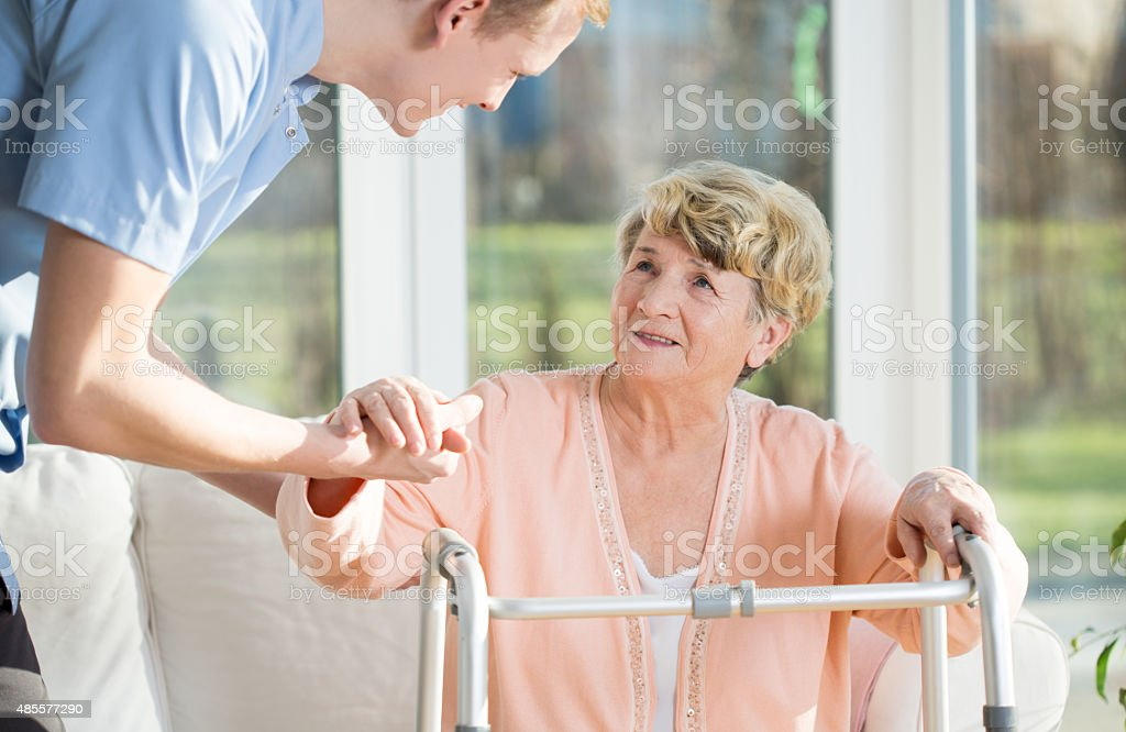 Man helps to stand up an older woman stock photo