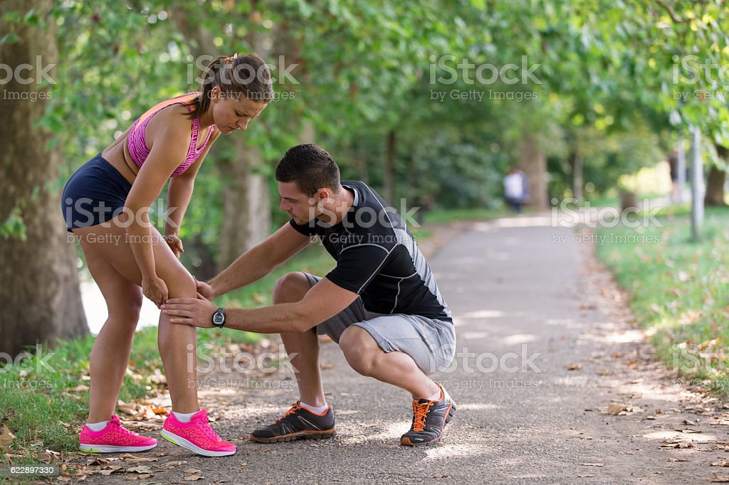 Man helps to woman with injured knee at sport activity stock photo