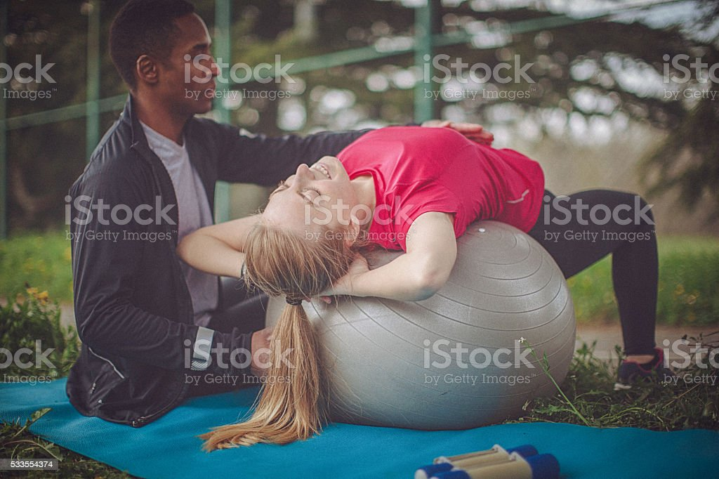 Man helps woman to correctly perform ab crunches on ball stock photo