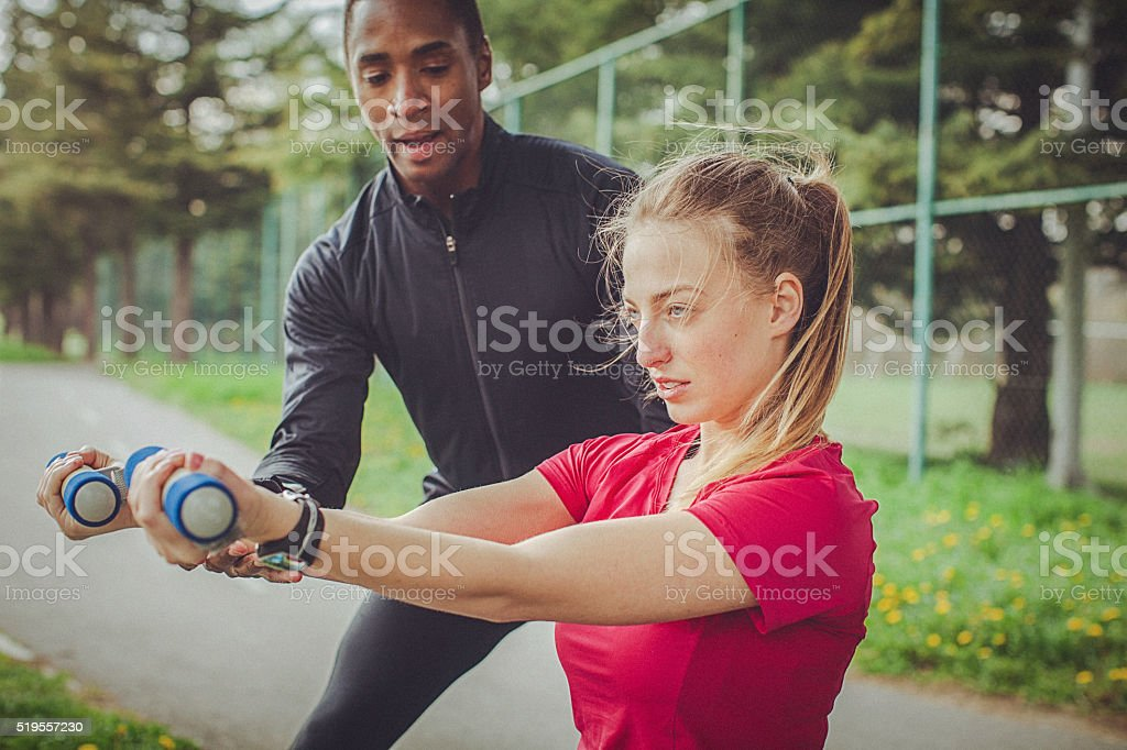 Man helps woman to correctly perform an exercise with dumbbells stock photo