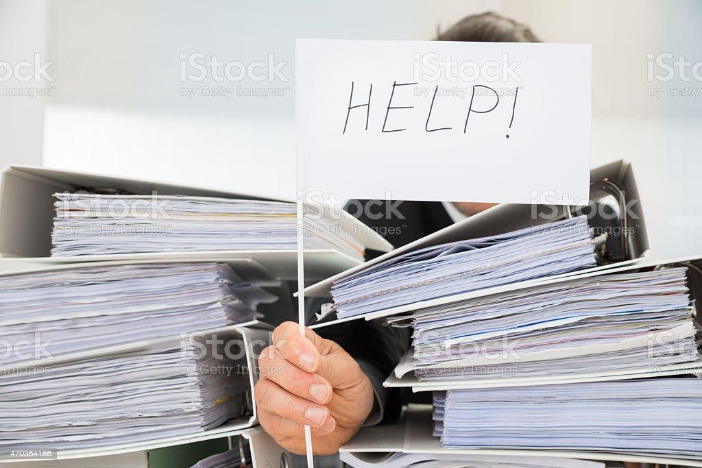 Man hidden behind stack of folders holding help flag stock photo