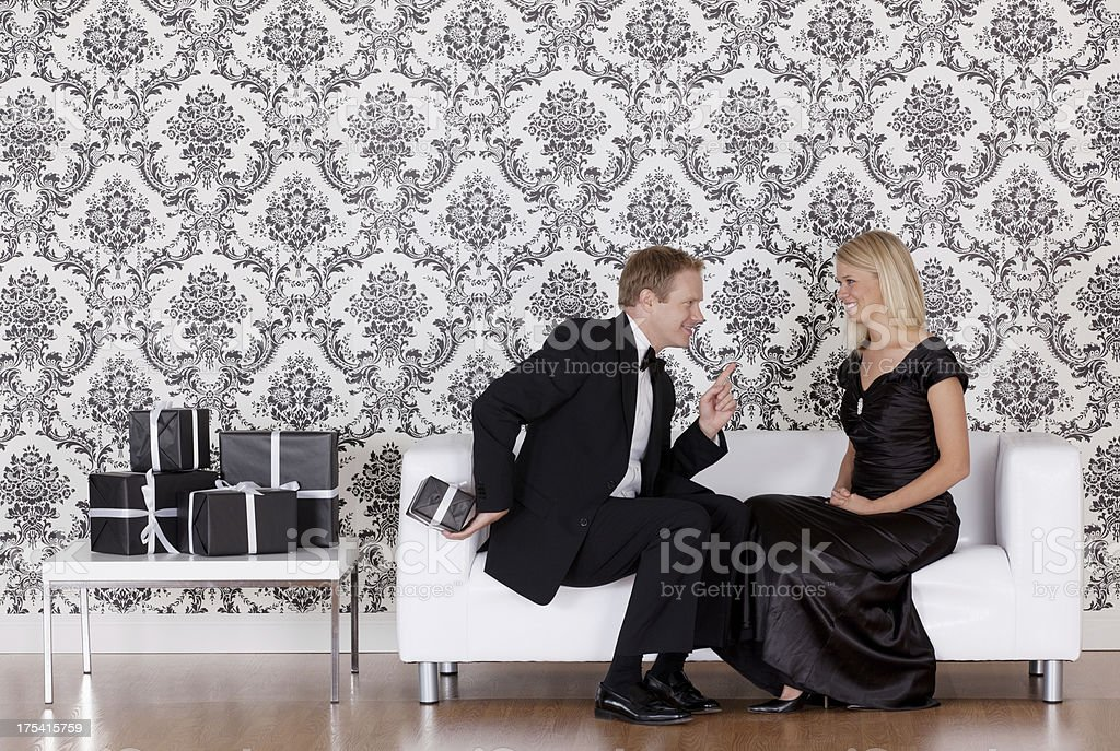 Man hiding a gift from his wife royalty-free stock photo