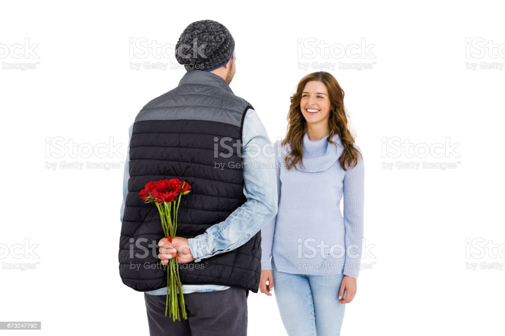 Man hiding a rose behind his back from his woman stock photo