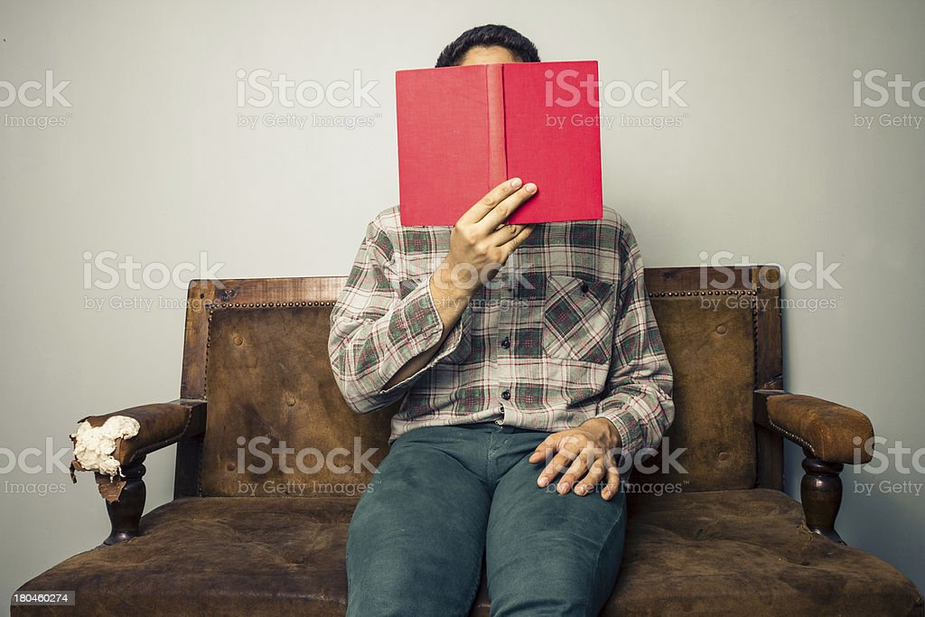 Man hiding behind book on old sofa royalty-free stock photo