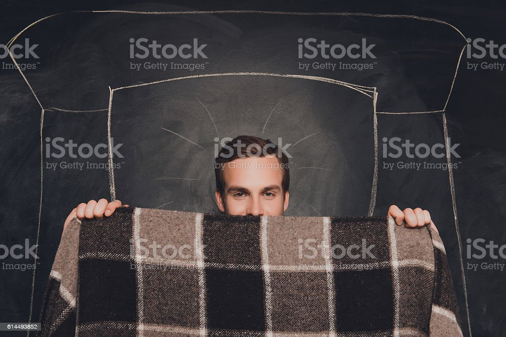 man hiding face behind plaid while  lying in painted bed stock photo