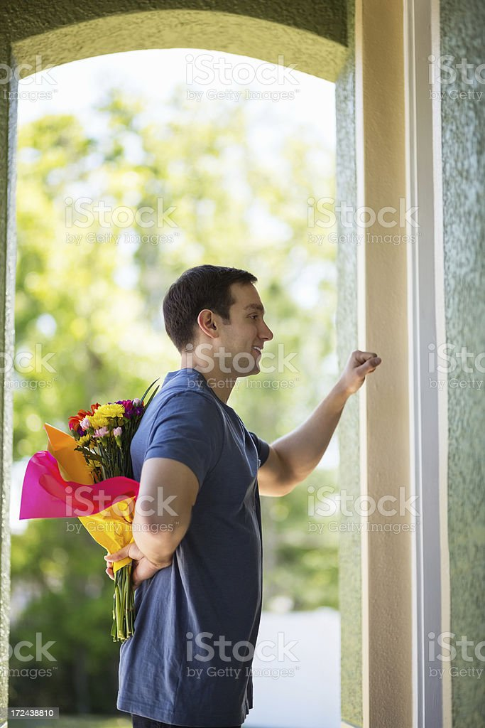 Man Hiding Flowers Behind Back While Knocking On Door royalty-free stock photo