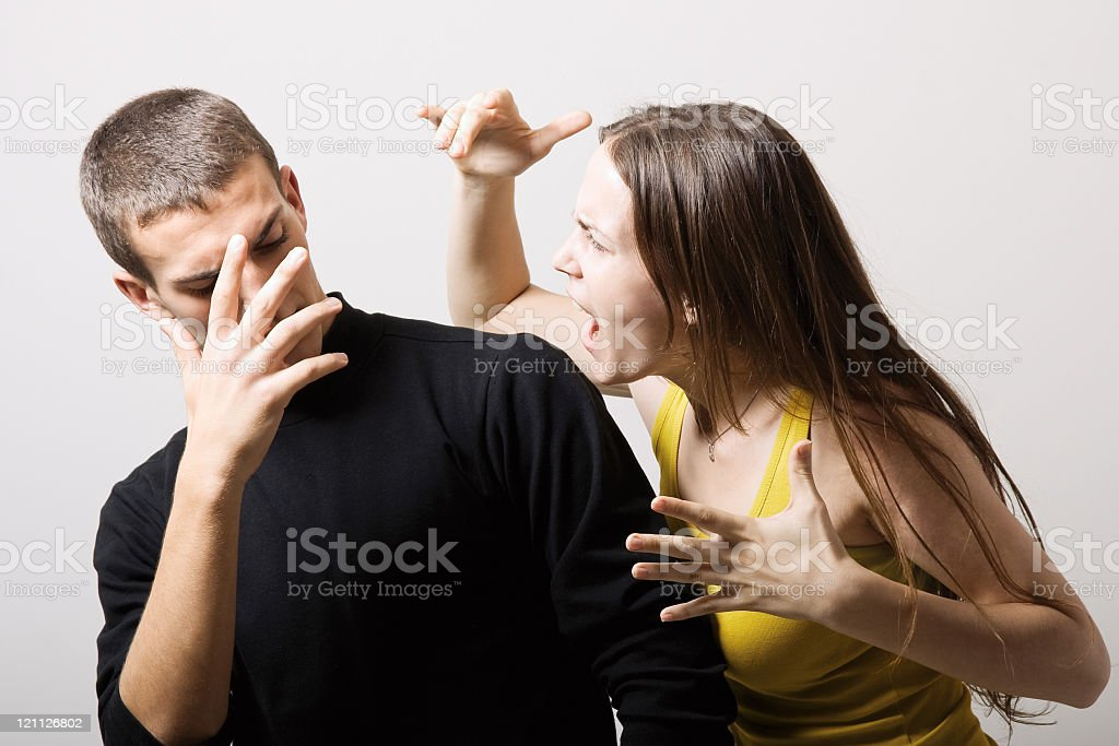 Man hiding his face and leaning away as woman screams at him royalty-free stock photo