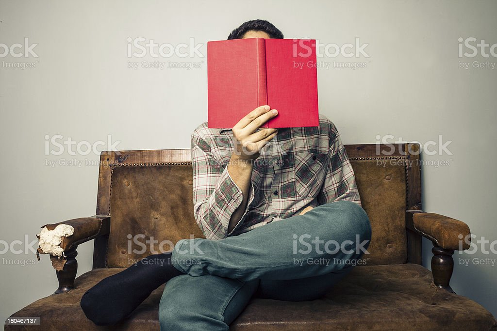 man hiding his face behind book on old sofa stock photo