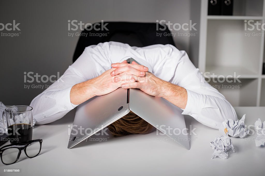 Man hiding under laptop stock photo