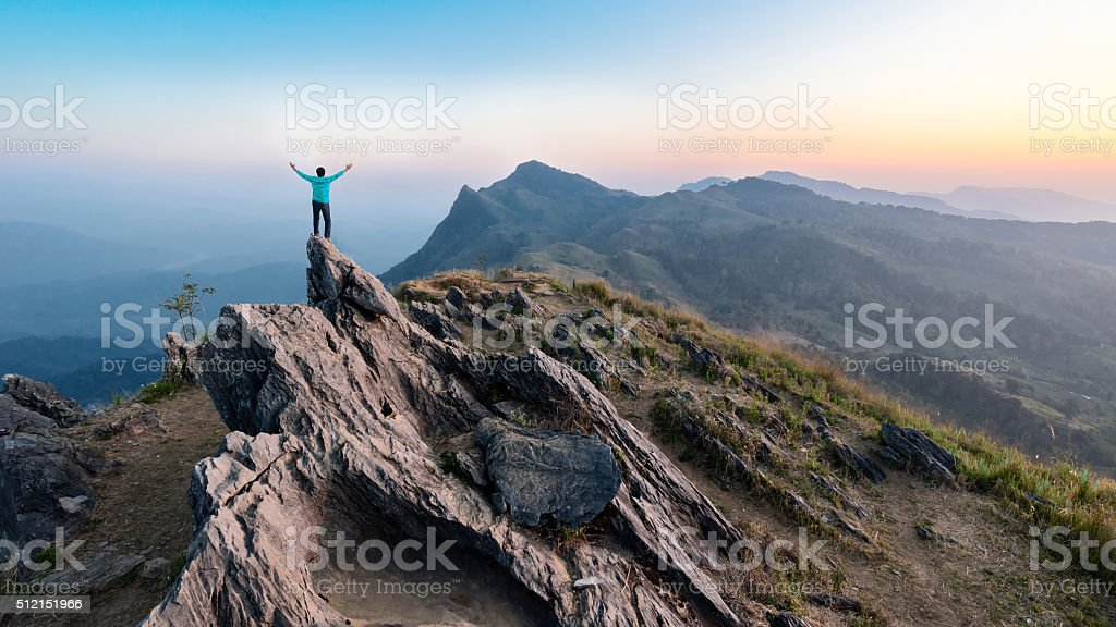 Man Hike on the peak of rocks mountain at sunset stock photo