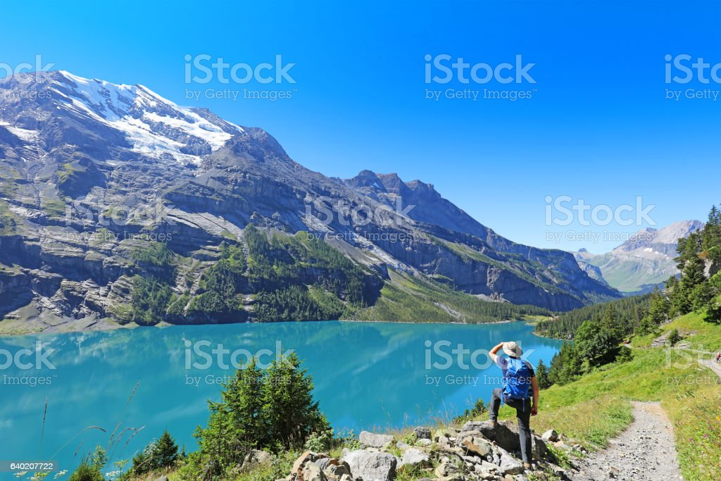 Man Hiker Admiring the  Mountain Scenics in the Swiss Alps stock photo