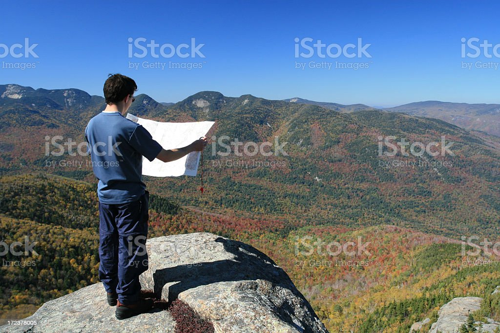 Man Hiker Looking at Map on Mountain Summit in Autumn royalty-free stock photo