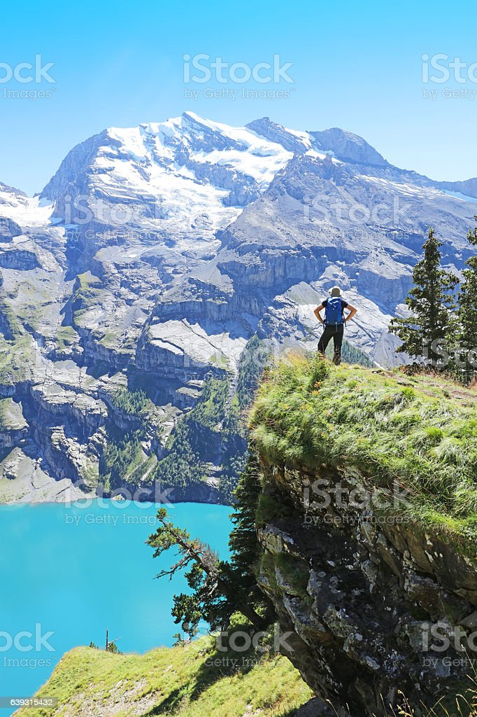 Man Hiker Looking at View over Oeschinensee Lake in Switzerland stock photo