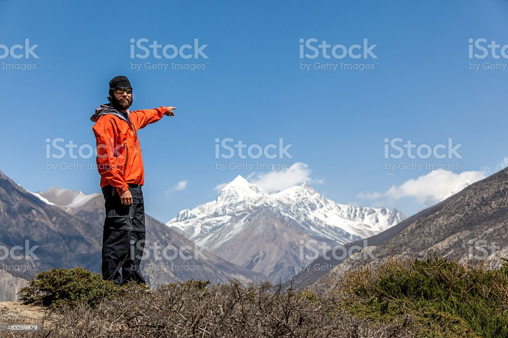 Man Hiker on Mountain Summit Pointing a Direction royalty-free stock photo