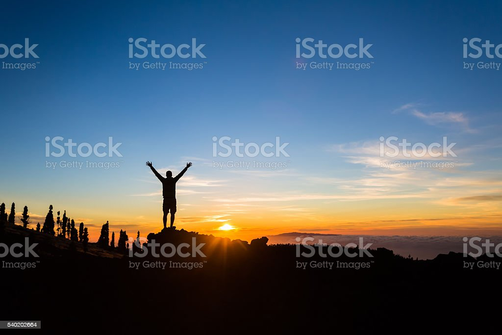 Man hiker silhouette with arms outstretched enjoy mountains stock photo