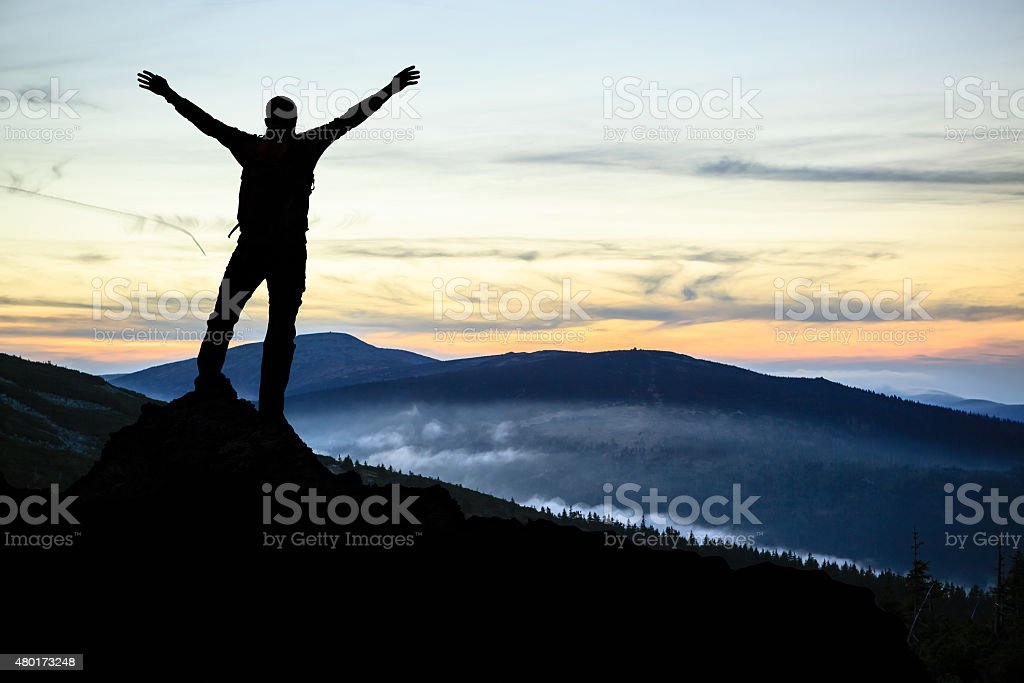 Man hiker successful with arms outstretched stock photo