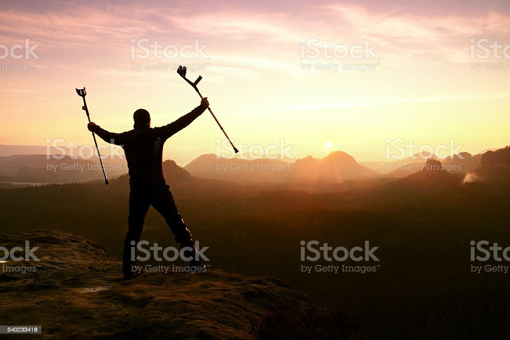 Man hiker with immobilizered  broken leg and medicine crutch. stock photo