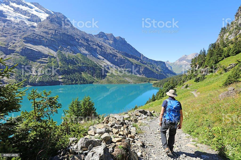 Man Hiking at Oeschinen Lake in Berner Oberland in Switzerland stock photo