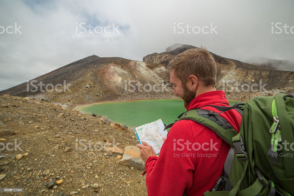 Man hiking by the lake looks at map stock photo