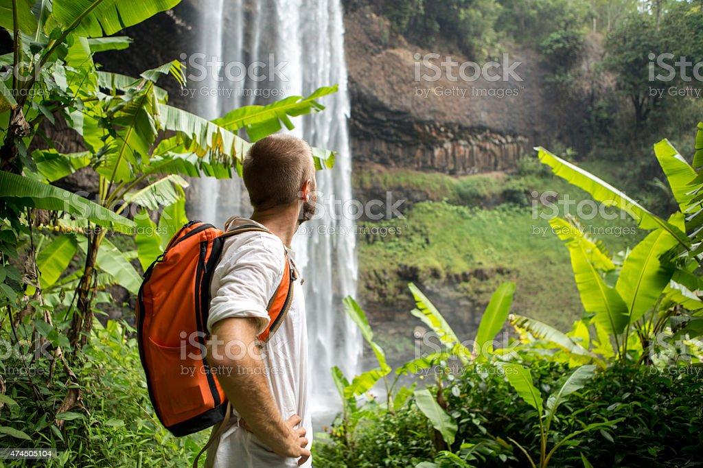 Man hiking in jungle looks at waterfall stock photo