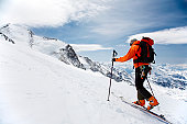 A man hiking in snowshoes up a snowy mountain