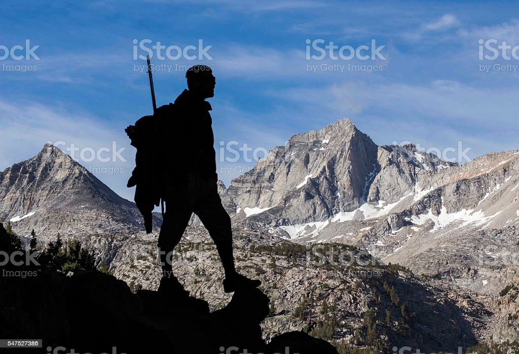 Man Hiking into the Mountains stock photo