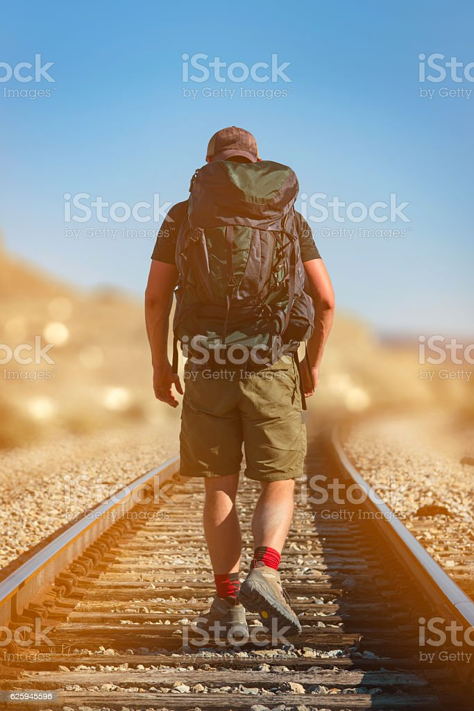 Man Hiking on Railroad Tracks stock photo
