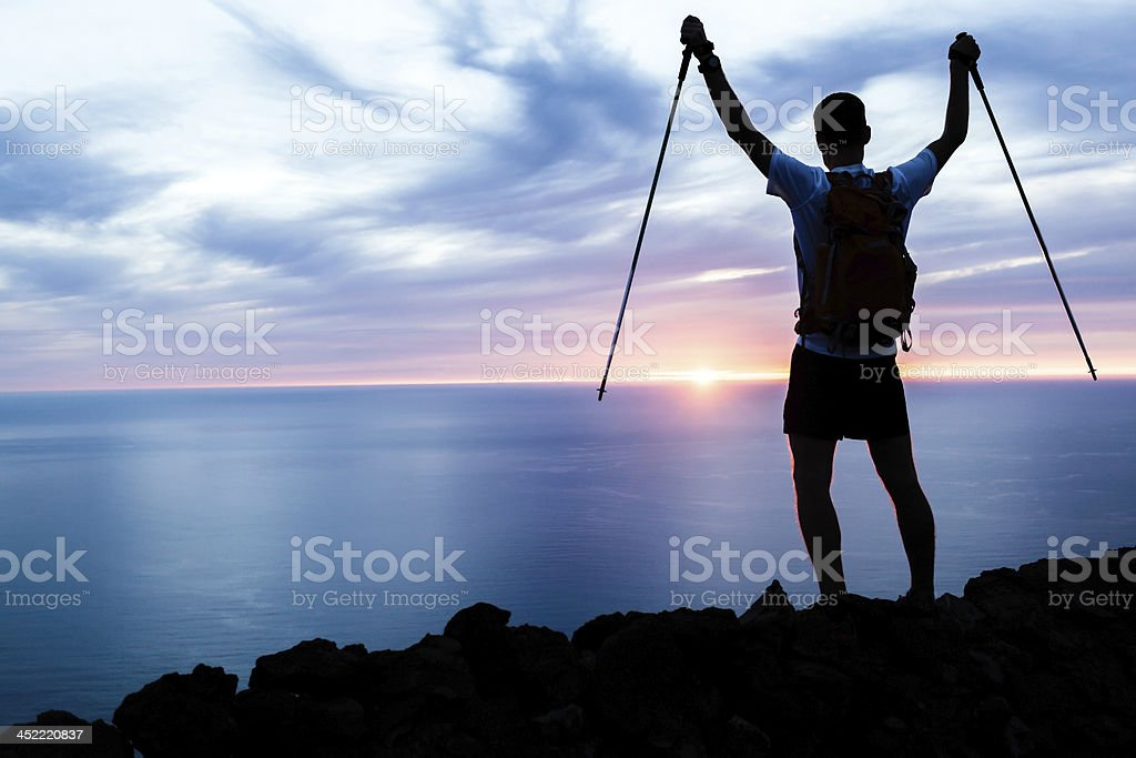 Man hiking silhouette in mountains, ocean and sunset royalty-free stock photo