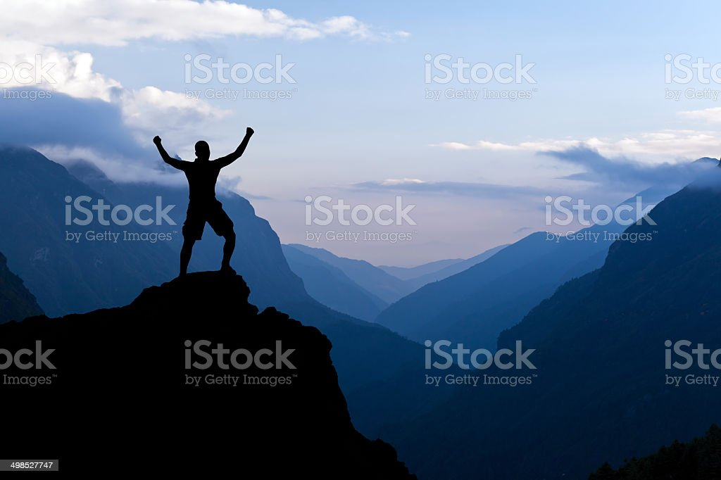 Man hiking success silhouette in mountains stock photo