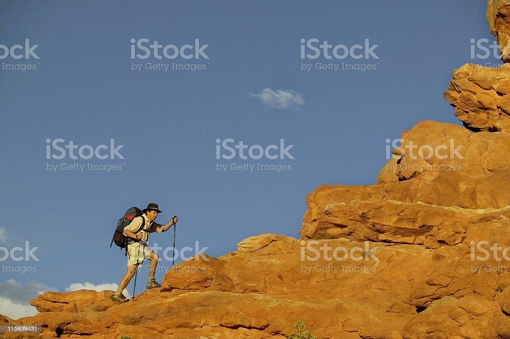 Man Hiking Up Rock Ledge stock photo