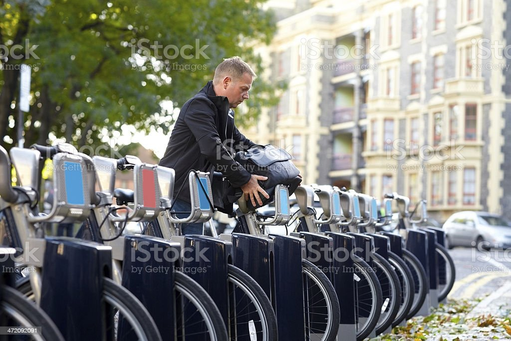 Man hiring a bicycle from cycle hire docking point stock photo