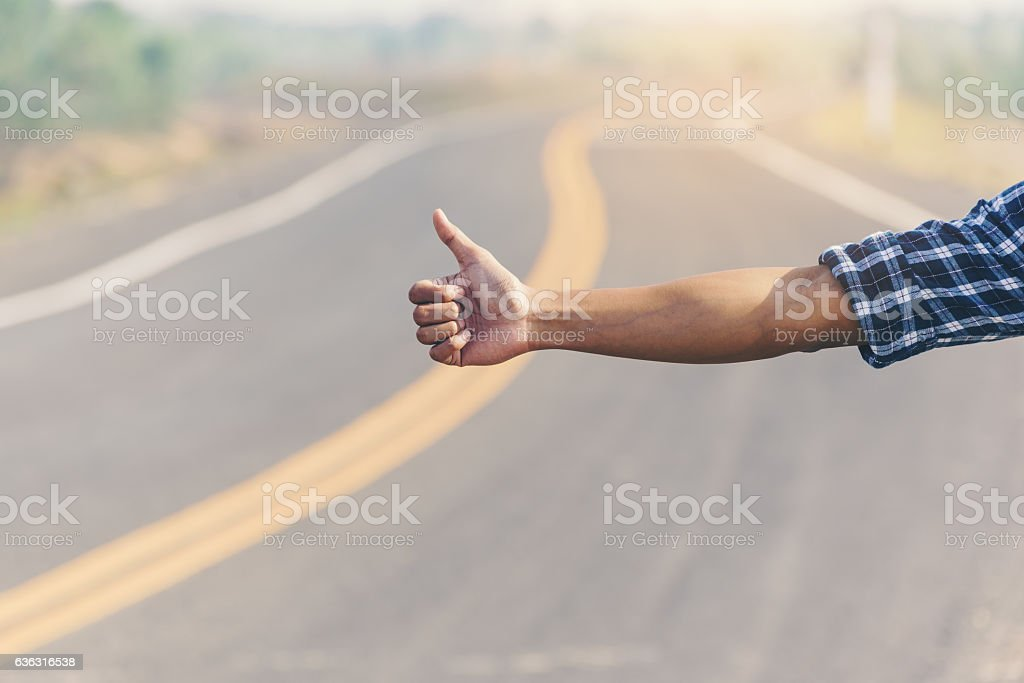 Man hitchhiker standing on a road. Adventure and tourism stock photo