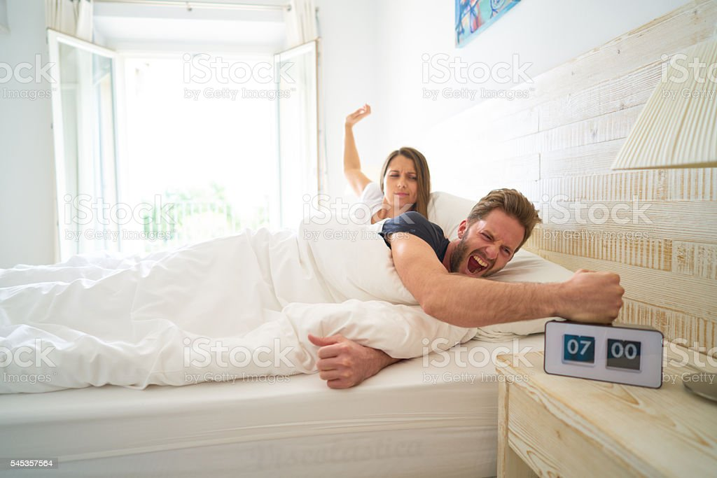 man hitting alarm clock stock photo