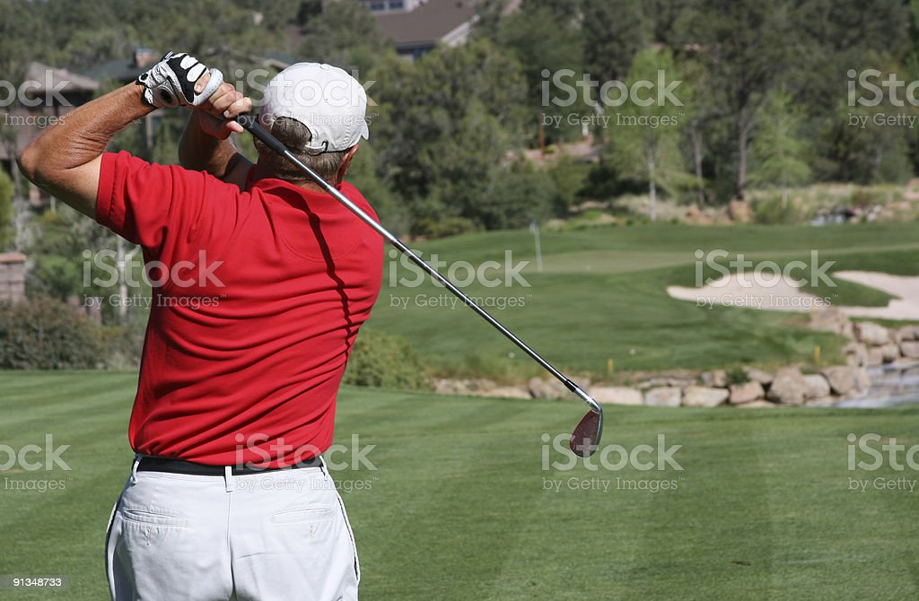 Man hitting ball to green, focus on golfer royalty-free stock photo